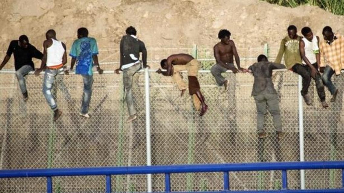 Migrants climb the border fence in Melilla, between Morocco and Spain