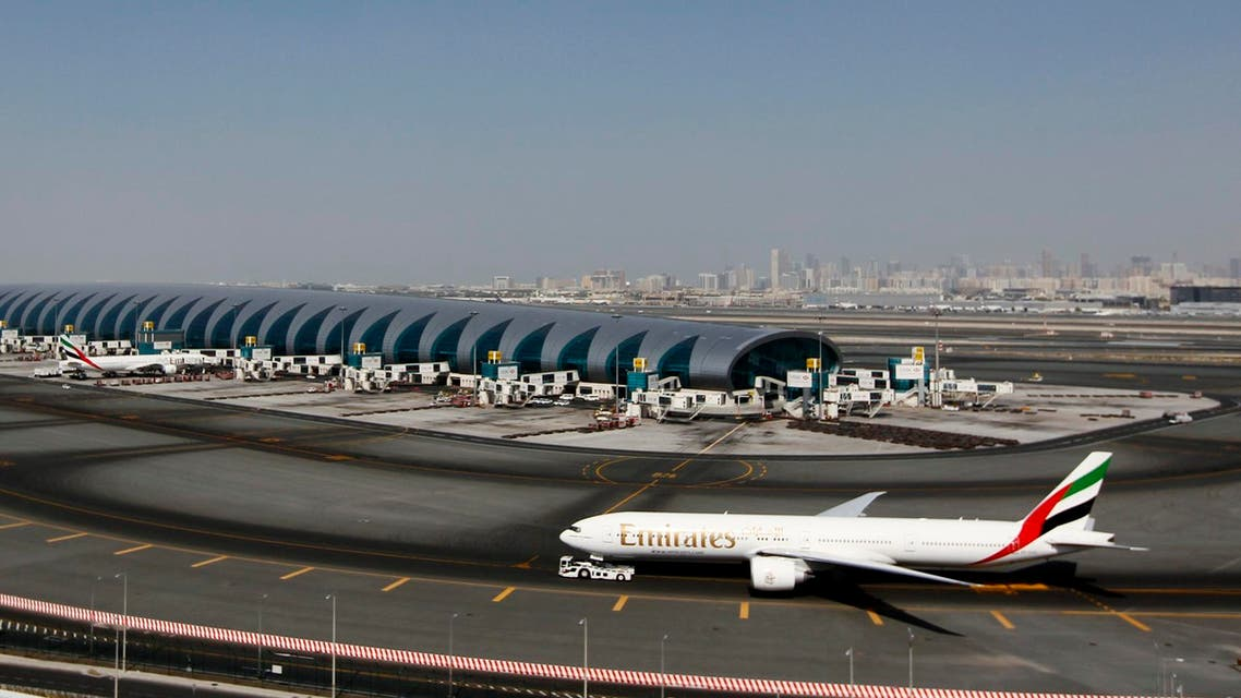 A plane passes next to the Emirates Airlines terminal at the concourse in Dubai International Airport, Jan. 7, 2013. (AFP)
