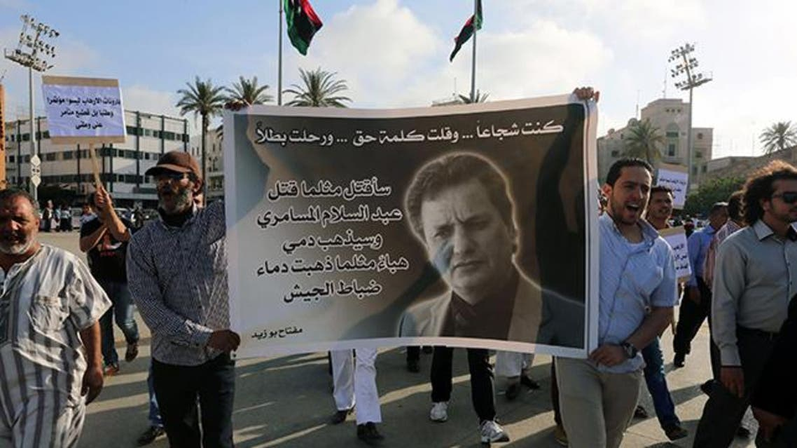 Protesters hold a banner bearing the portrait of Miftah Bouzeid, editor of the weekly newspaper Burniq, during a rally in Tripoli's Martyrs' Square  AFP