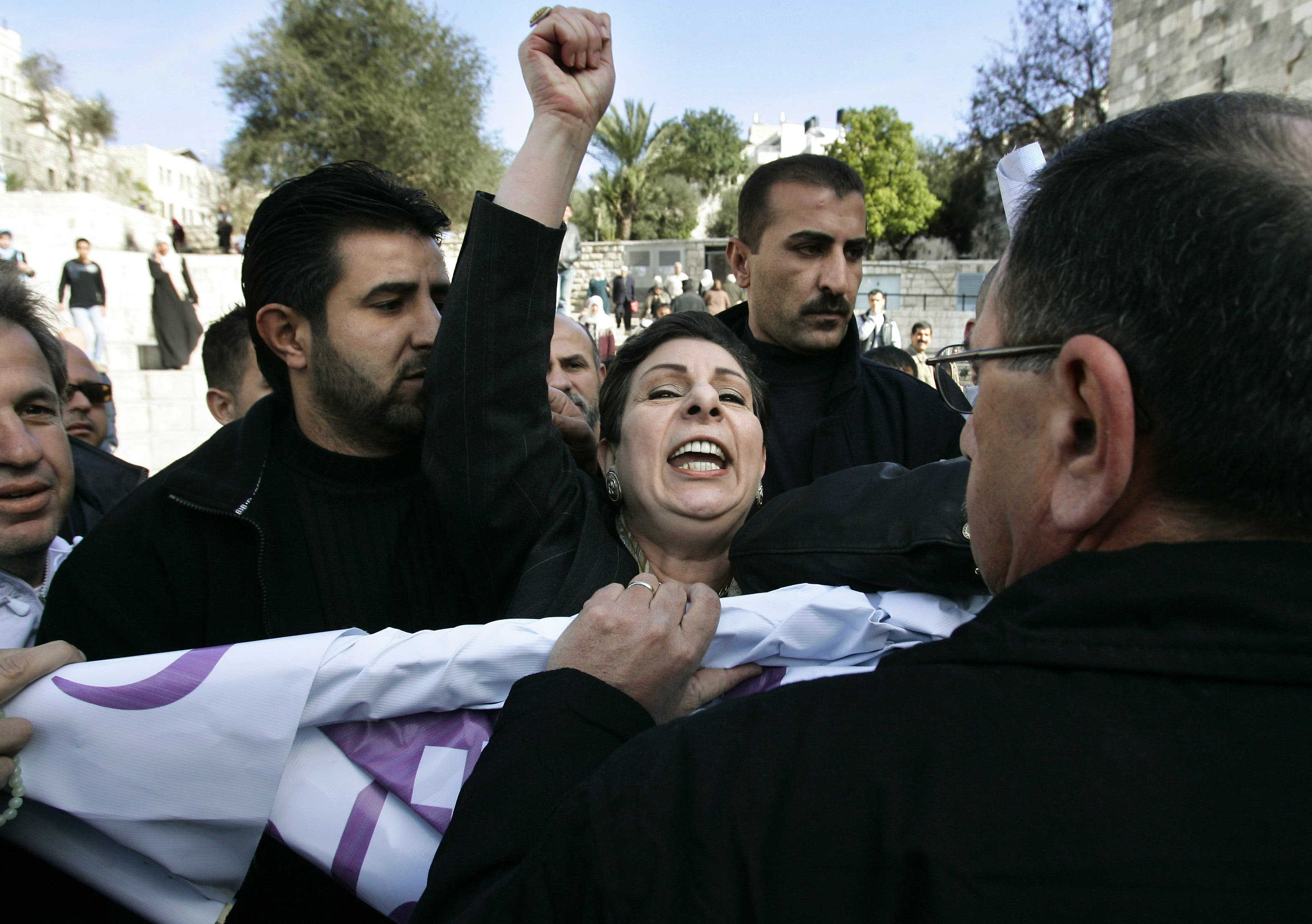 Palestinian parliamentary election candidate Hanan Ashrawi, center, from the Third Way party shouts as she and supporters scuffle with Israeli police officers, right, as they take her election banner from her during a campaign stop in front of Damascus Gate in Jerusalem's Old City, Tuesday, Jan. 3, 2006. (AP)