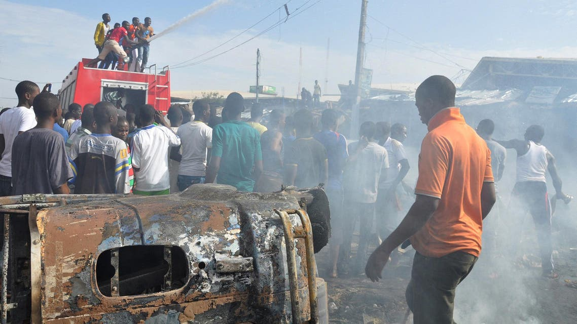 In this Tuesday, July , 2014 file photo, People gather at the scene of a car bomb explosion, at the central market, in Maiduguri, Nigeria. AP