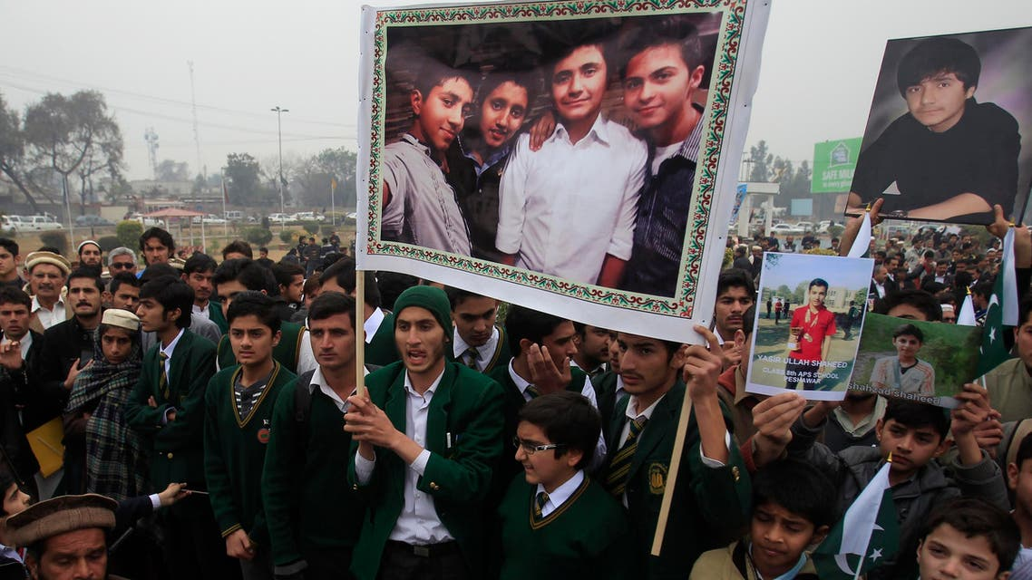 Students hold photographs of their schoolmates, who were killed in an attack by Taliban gunmen on Army Public School (APS), during a protest along with relatives of the victims, demanding an investigation to bring the killers to justice, in Peshawar February 7, 2015. Reuters