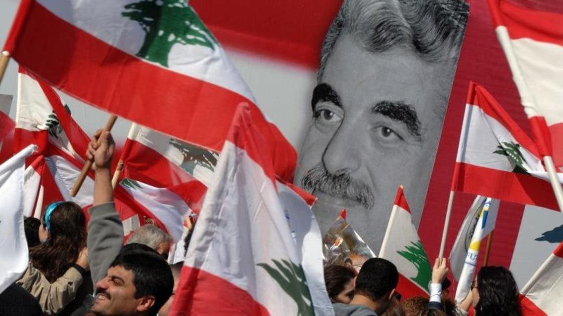 Lebanese government supporters hold Lebanese flags as they attend a rally to commemorate the death of former Prime Minister Rafik Hariri (pictured in the background) in downtown Beirut, Lebanon Wednesday, Feb. 14, 2007. AP