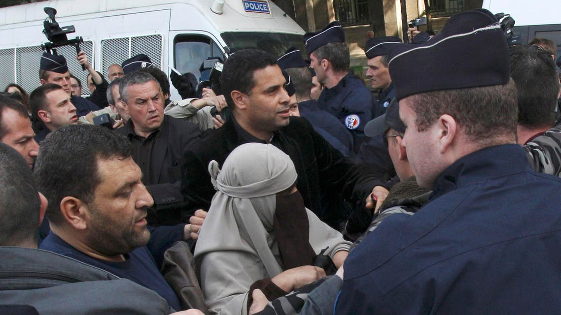An unidentified veiled woman is taken away by plain clothed and uniformed police officers, flanked by a friend, center right, in Paris Monday, April 11, 2011. AP