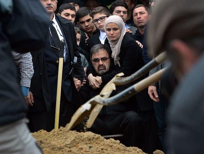 نعمة بركات، من ادلب في سوريا، يبدو وخلفه ابنته سوزان أمام قبر ابنه ضياء