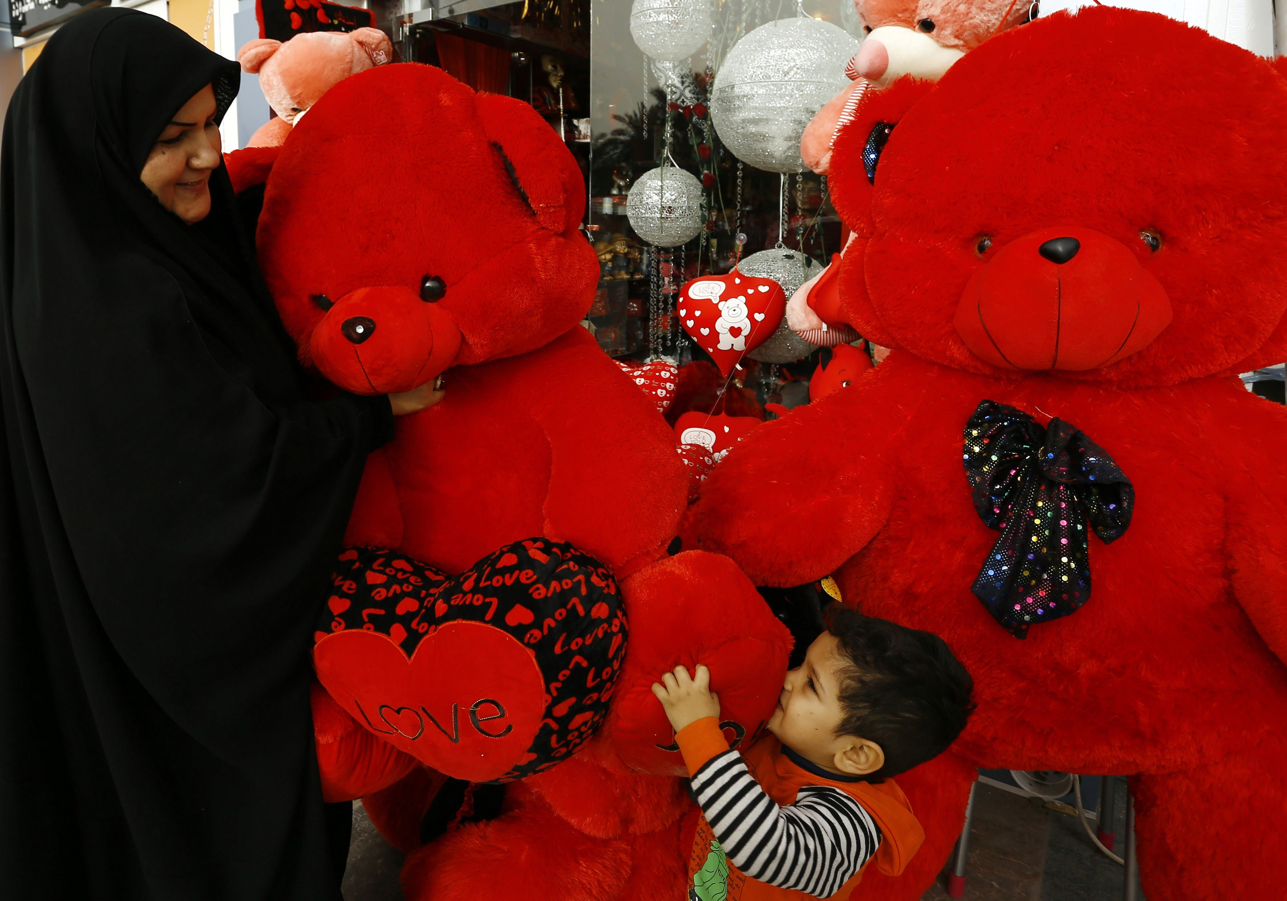 An Iraqi woman and child hold a teddy bear as they shop for gifts ahead of Valentine's Day in the central Iraqi city of Najaf on February 12, 2015. AFP PHOTO