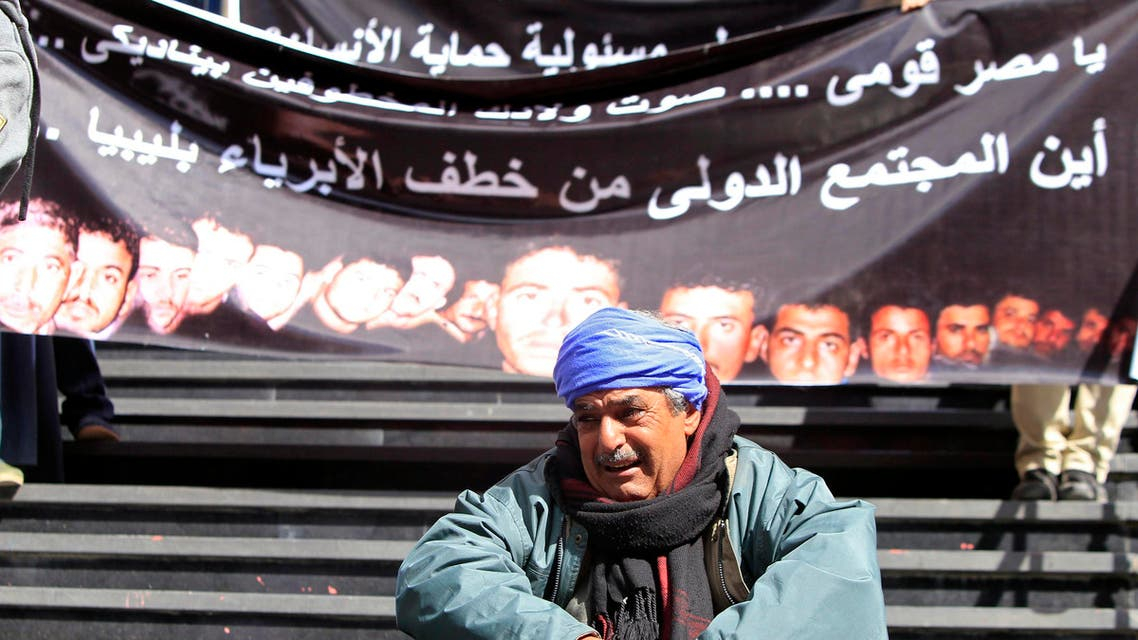 A family member of one of  Egyptian Coptic Christian workers who have been kidnapped in the Libyan city of Sirte, sits crying in front of a banner with pictures of the workers, in Cairo, Feb. 13, 2015. (Reuters)