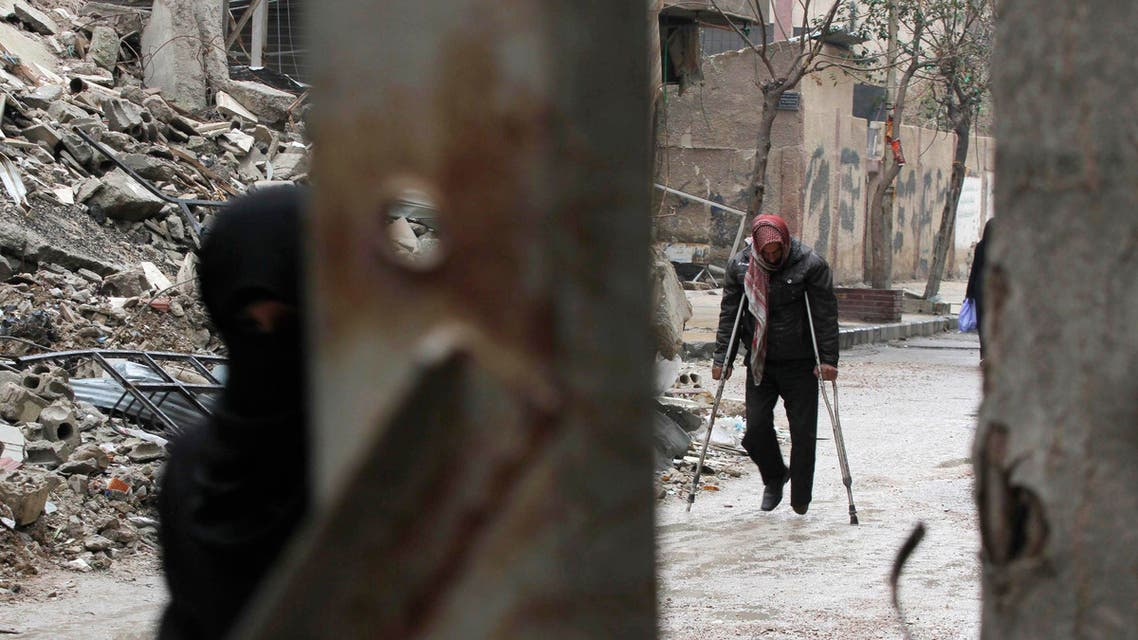 A man walks on crutches near the rubble of collapsed buildings in the Douma neighbourhood of Damascus February 12, 2015. (Reuters)