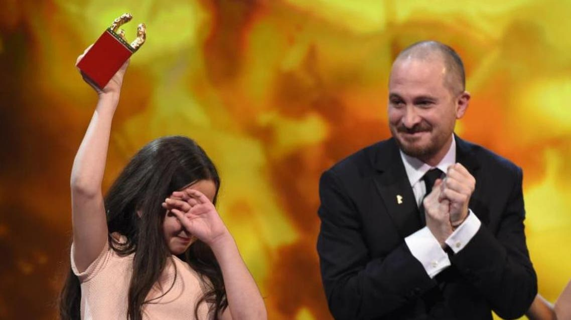 The niece of Iranian director Jafar Panahi holds the Golden Bear trophy she accepted in his place at the 65th International Film Festival Berlinale next to jury president Darren Aronofsky on February 14, 2015 in Berlin (AFP Photo/Tobias Schwarz)