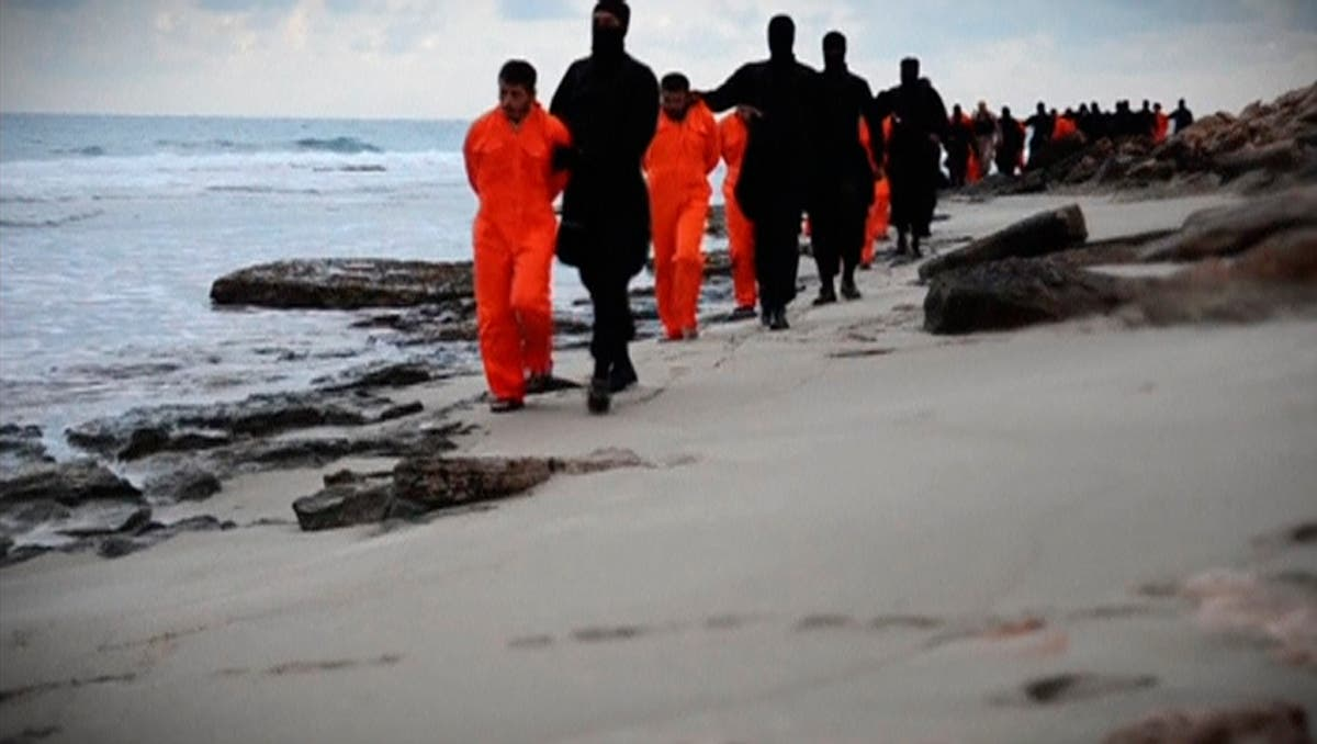 Men in orange jumpsuits purported to be Egyptian Christians held captive by the ISIS are marched by armed men along a beach said to be near Tripoli, in this still image from an undated video made available on social media on February 15, 2015. (Reuters)