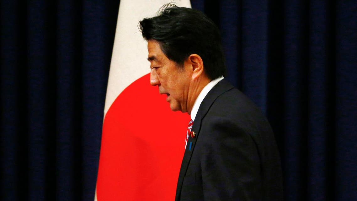 Japan's Prime Minister Shinzo Abe passes by a Japanese flag after a news conference in Beijing reuters