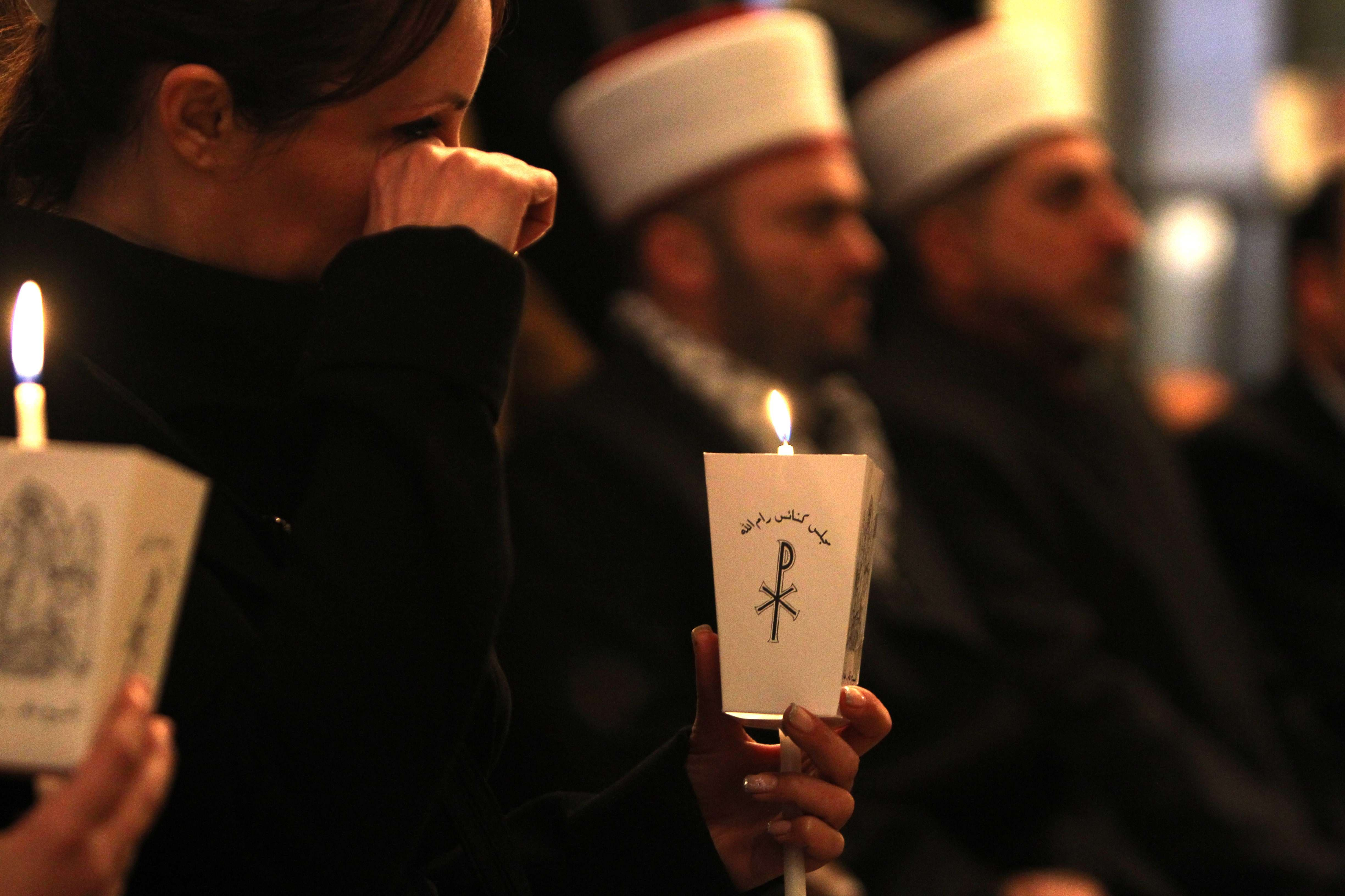 Christian and Muslim Palestinians attend a memorial ceremony in the West Bank of Ramallah on February 17, 2015, for the Egyptian Coptic Christians murdered by Islamic State (IS) group militants in Libya.