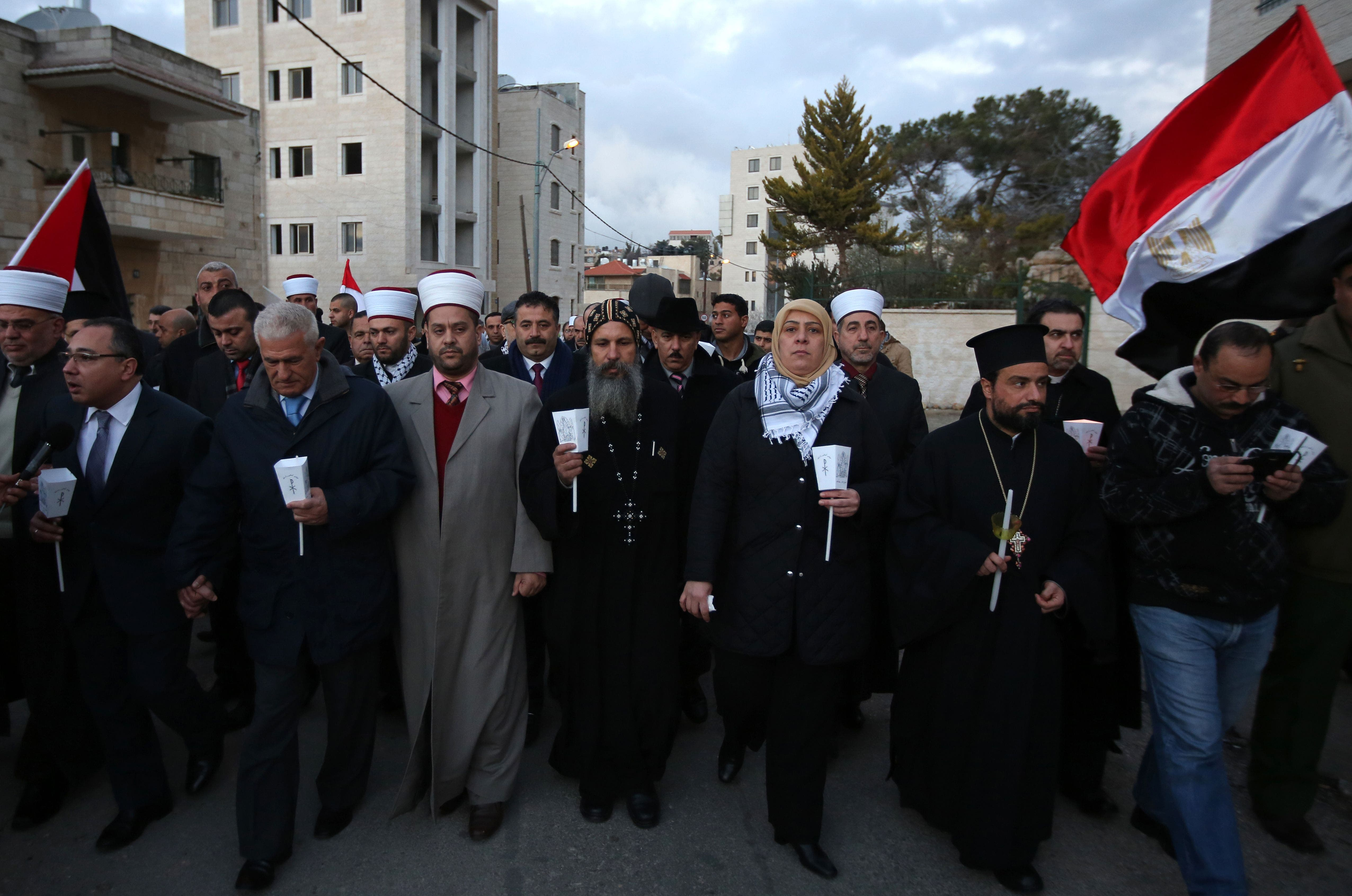Christian and Muslim Palestinians take part in a rally in the West Bank of Ramallah on February 17, 2015, in memory of the Egyptian Coptic Christians murdered by Islamic State (IS) group militants in Libya. AFP
