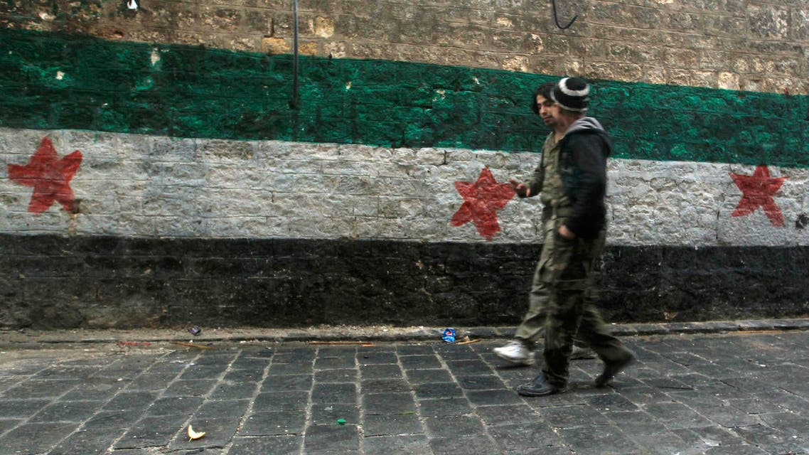 Free Syrian Army fighters walk beside a Free Syrian Army flag painted on a wall in Aleppo January 23, 2015.