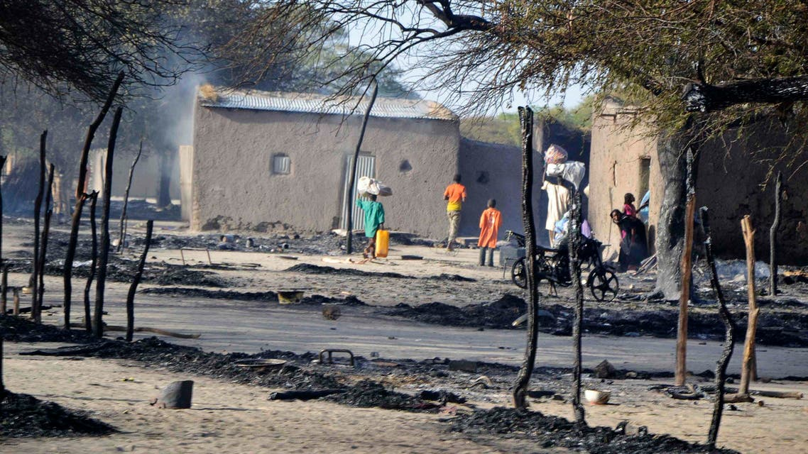 People walk in a burnt compound after an attack by Boko Haram militants in the village of Ngouboua Feb. 13, 2015. (Reuters)
