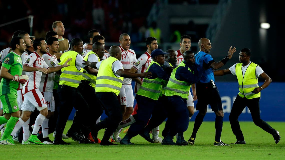 Referee Rajindraparsad Seechurn, second from right, is shielded by security personal against the Tunisia's player at the end of the African Cup of Nations quarter final soccer match against Equatorial Guinea in Bata, Equatorial Guinea, Saturday, Jan. 31, 2015. (AP)
