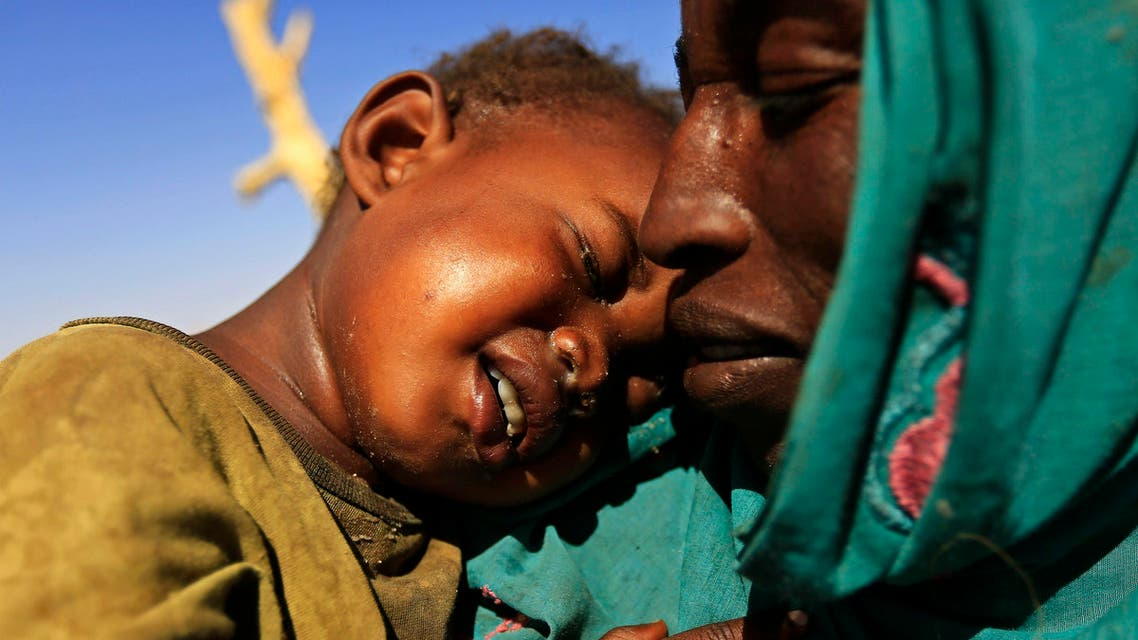 A woman carrying a child arrives at the Zamzam IDP camp for Internally Displaced Persons (IDP), near El Fasher in North Darfur February 4, 2015. (Reuters)