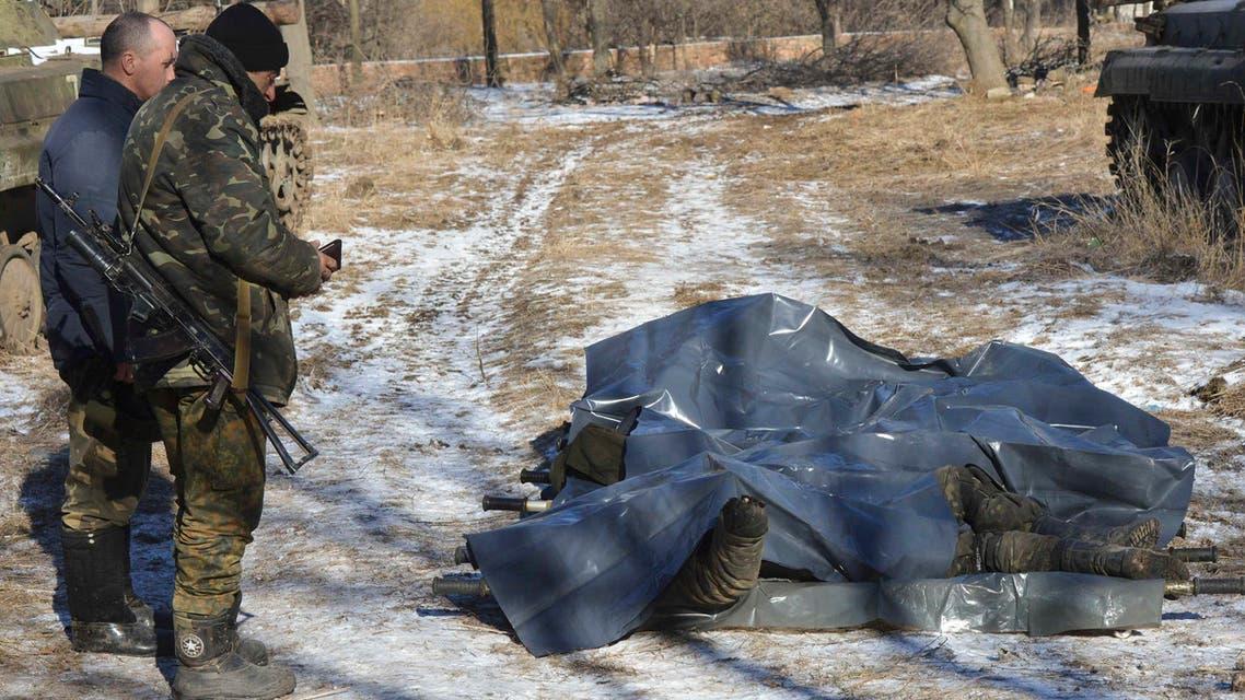 جنديان أوكرانيان يقفان أمام جثث رفاقهما في ديبالتسيفي