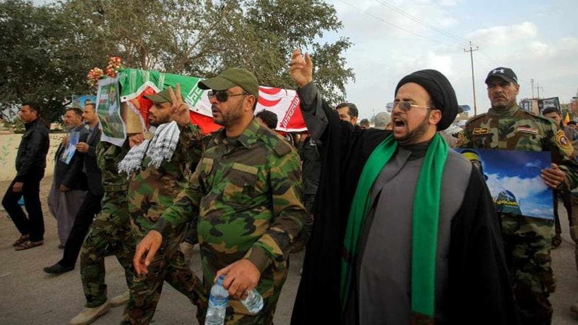 Iranian cleric Mohammed Jafari, second right, and Shiite militiamen chant slogans against ISIS as they carry a coffin draped with the Iranian flag during a funeral procession for Mohammad Hadi Zulfiqar, in the poster, an Iranian volunteer fighting in the Badr Brigades Shiite militia, in Najaf, 100 miles (160 kilometers) south of Baghdad, Iraq, Thursday, Feb. 19, 2015. (AP)