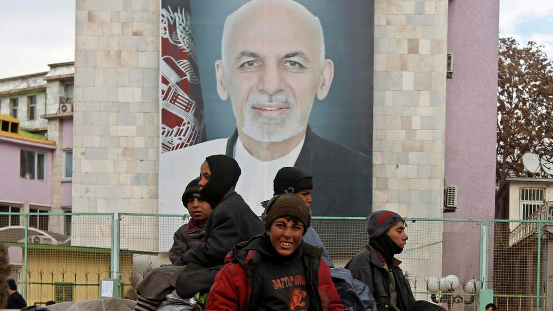Afghan youths sit on the roof of a car as they pass a picture of Afghan President Ashraf Ghani on a street in Kabul February 19, 2015. (Reuters)