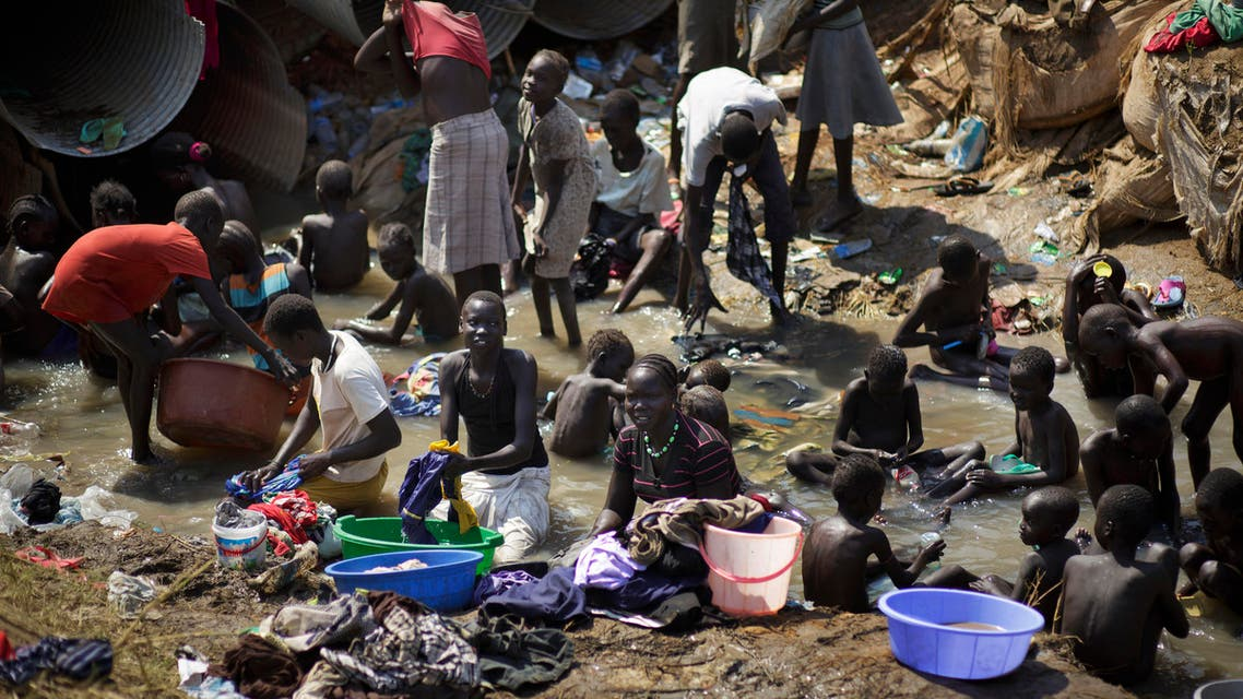 In this Friday Dec. 27 , 2013 file photo, displaced people bathe and wash clothes in a stream inside a United Nations compound which has become home to thousands of people displaced by the recent fighting, in Juba, South Sudan. AP