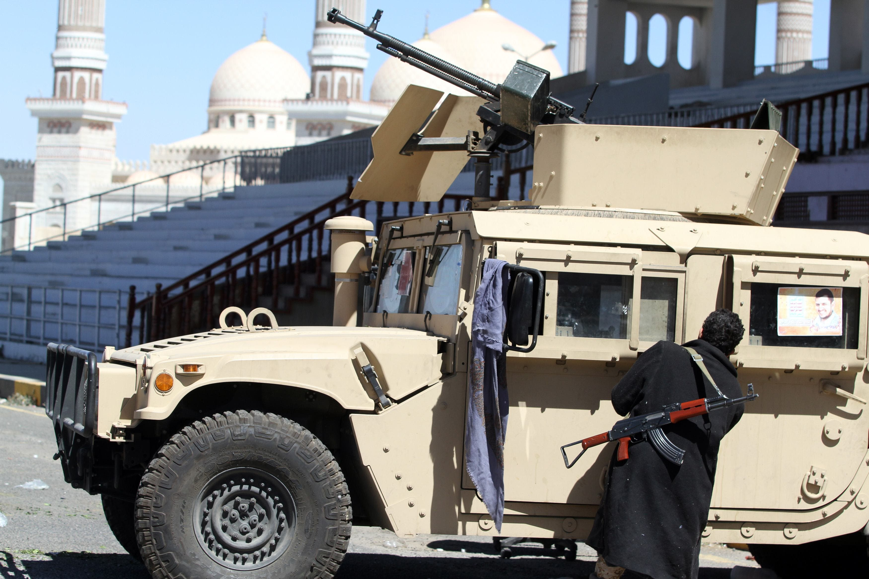A Houthi fighter opens the door of a military vehicle which was seized from the army during recent clashes, outside an entrance to the presidential palace in Sanaa January 29, 2015. (Reuters)