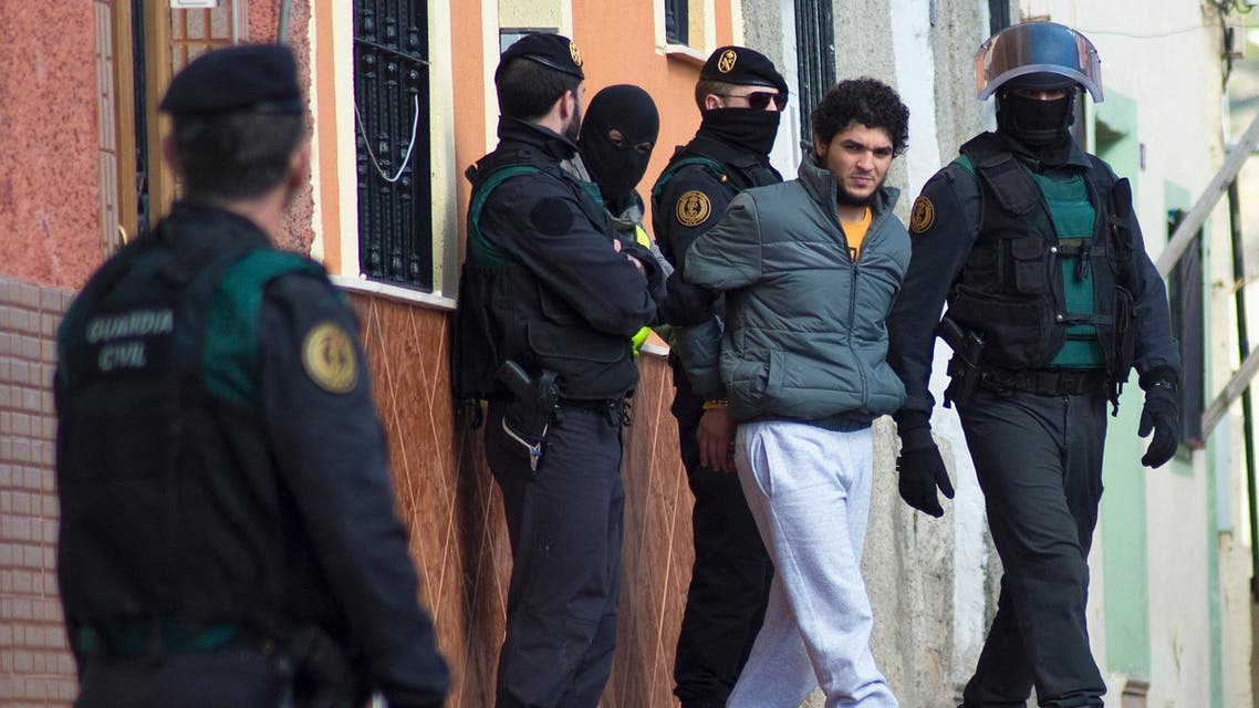 Spanish civil guards lead a detained man suspected of using social media to recruit people to violent groups like the Islamic State, in Spain's North African enclave Melilla, February 24, 2015. Reuters