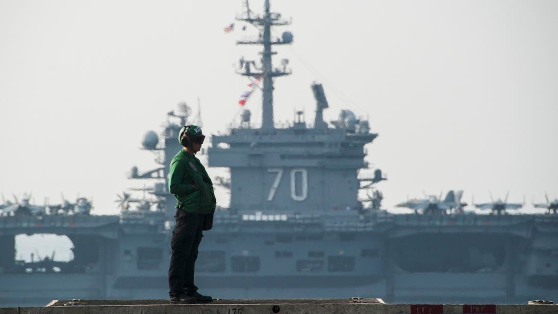 In this Oct. 18, 2014 photo provided by the U.S. Navy, the aircraft carrier USS Carl Vinson, background, sails beside the aircraft carrier USS George H.W. Bush in the Persian Gulf. (AP)