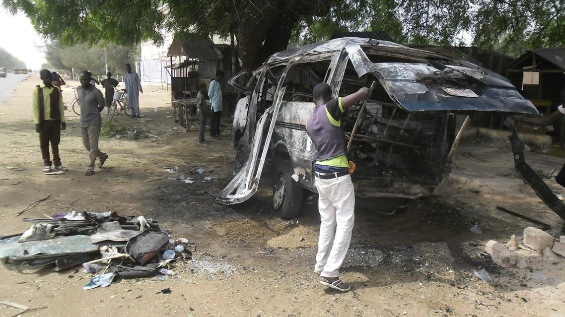 A man inspects a bus following an explosion on the street in Potiskum, Nigeria. Tuesday, Feb. 24, 2015 . AP