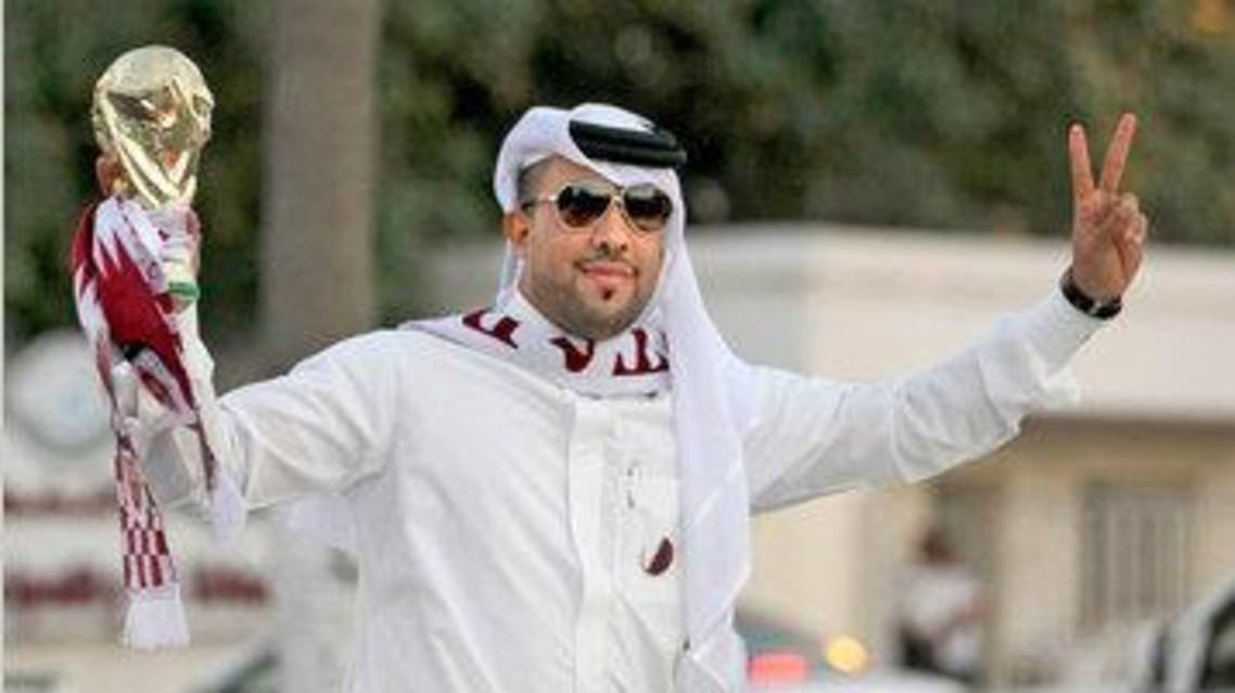 A Qatari fan holds a replica of the World Cup trophy as he celebrates in Doha