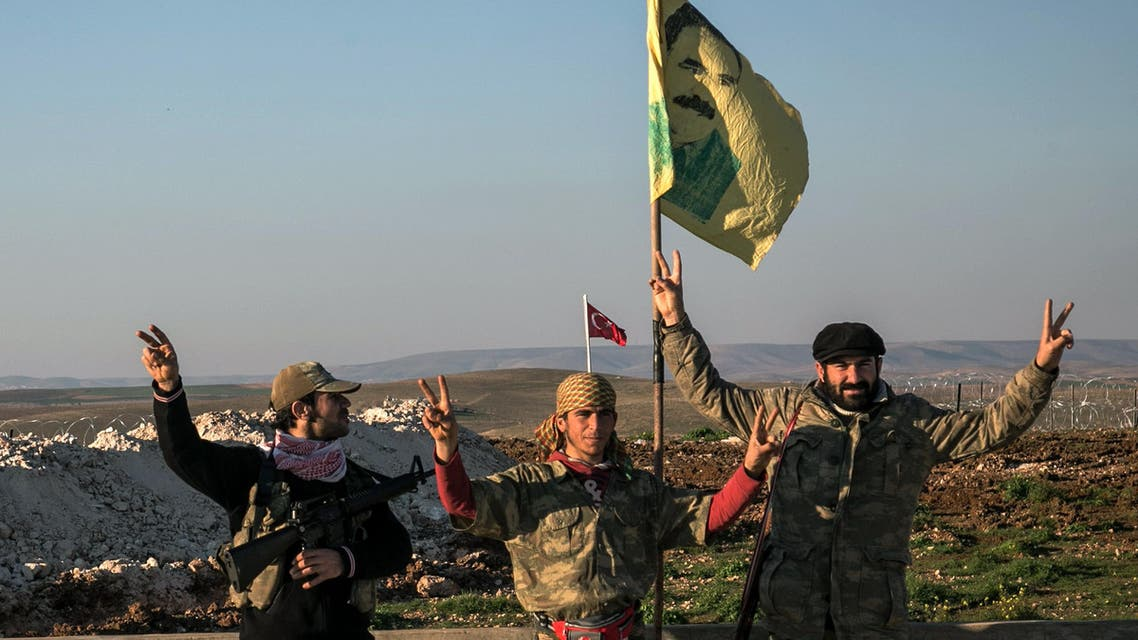 Syrian Kurdish militia members of YPG make V-sign next to poster of Abdullah Ocalan, jailed Kurdish rebel leader, and a Turkish army tank in the background in Esme village in Aleppo province, Syria, Sunday, Feb. 22, 2015. (AP)