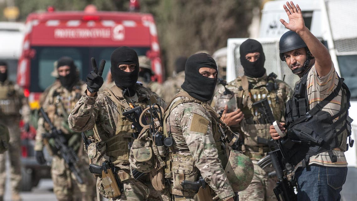 Tunisian soldiers celebrate at the end of a successful raid against gunmen in the Oued Ellil suburb of Tunis, Tunisia, Friday, Oct. 24, 2014. AP