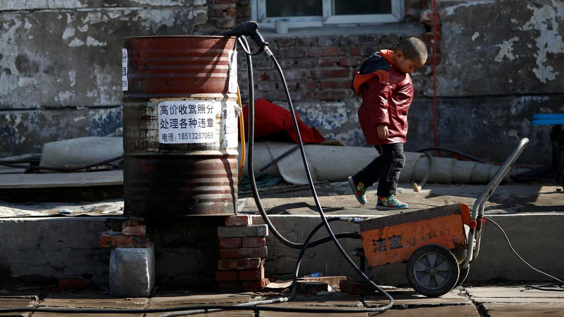 A boy walks past an oil barrel which is being used as a water bucket at a car wash in a migrant workers' village in Beijing February 12, 2015. (Reuters)