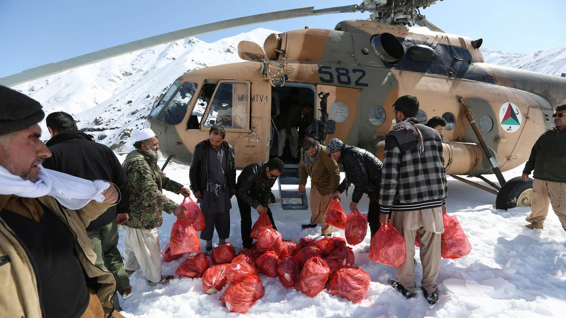 Afghans carry emergency food to a helicopter to deliver to avalanche survivors in Panjshir province, north of Kabul, Afghanistan, Friday, Feb. 27, 2015. AP