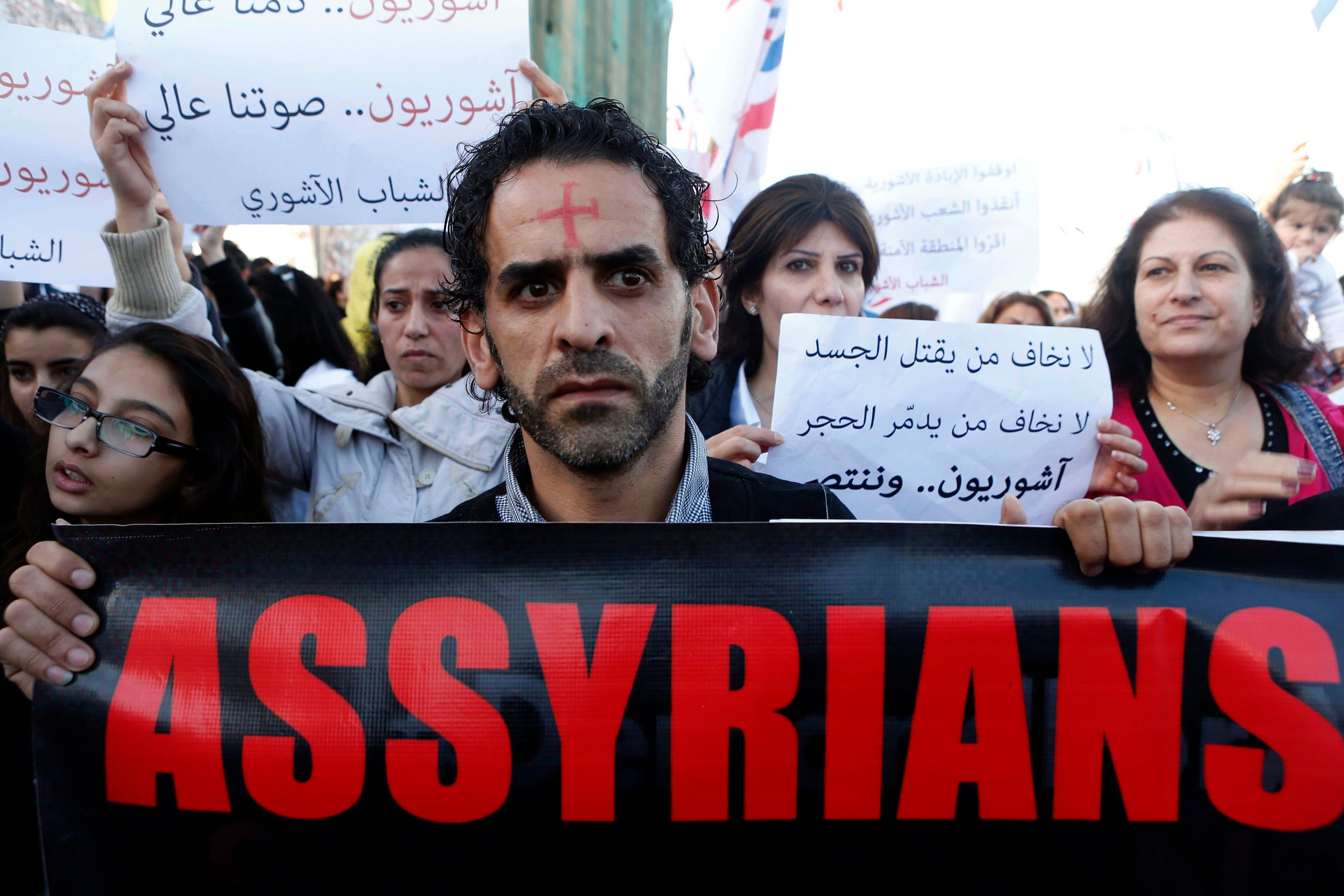 Assyrian hold placards during a gathering, on February 28, 2015 in the Lebanese capital Beirut. (Reuters)