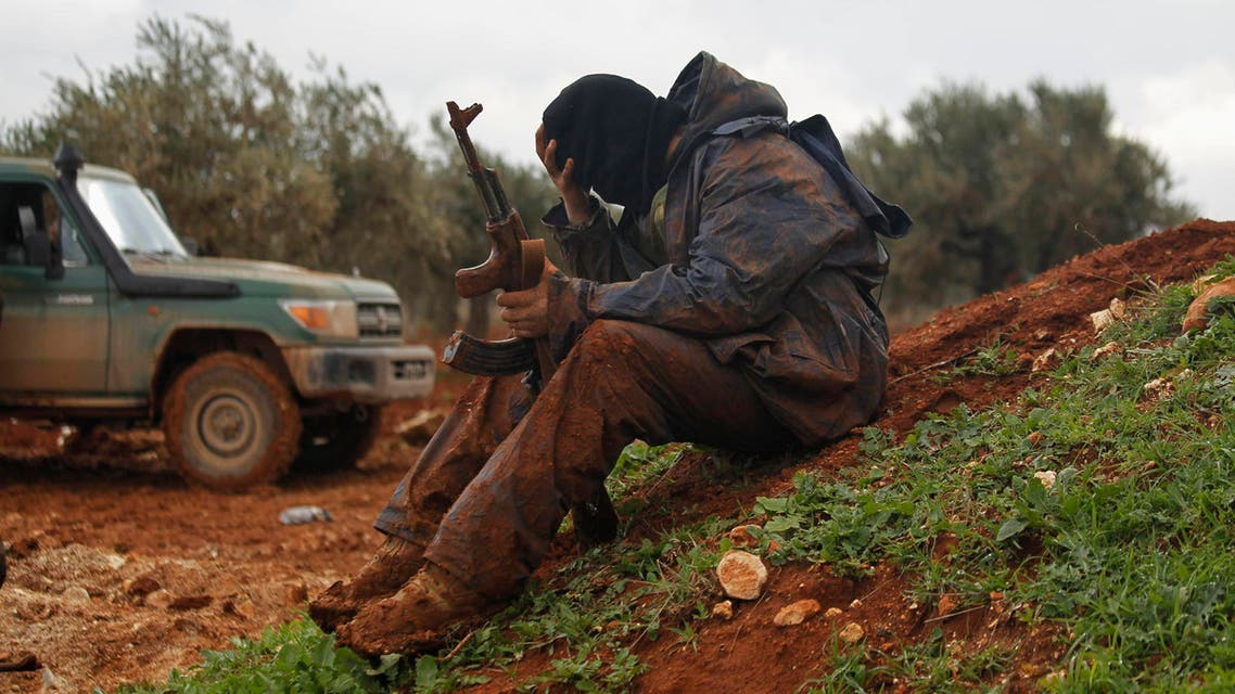 A rebel fighter of al-Jabha al-Shamiya (the Shamiya Front) covered with mud carries his weapon as he sits near the front line with Bashkuwi village, north of Aleppo February 19, 2015. (Reuters)