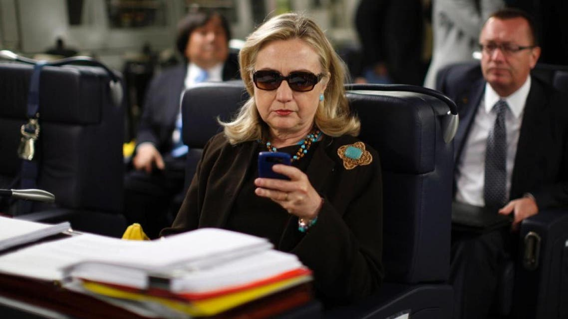 Former Secretary of State Hillary Clinton using her phone on a flight to Libya, in a picture that became widely popular. (Reuters)