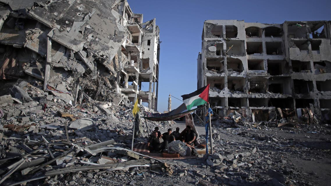 In this Aug. 11, 2014 file photo, Palestinian Ziad Rizk, 38, sits with others in a shelter made of a blanket stretched over four boles next to one of the destroyed Nada Towers, where he lost his apartment and clothes shop. (AP)