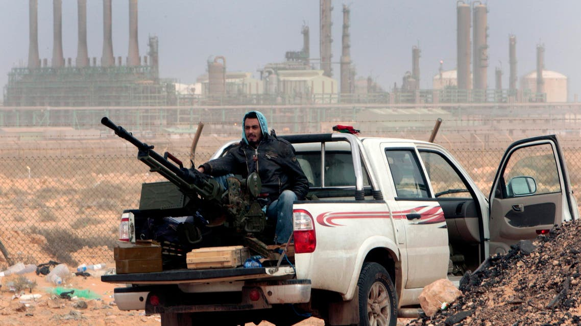 an anti-government rebel sits with an anti-aircraft weapon in front an oil refinery, after the capture of the oil town of Ras Lanouf, eastern Libya. (AP)