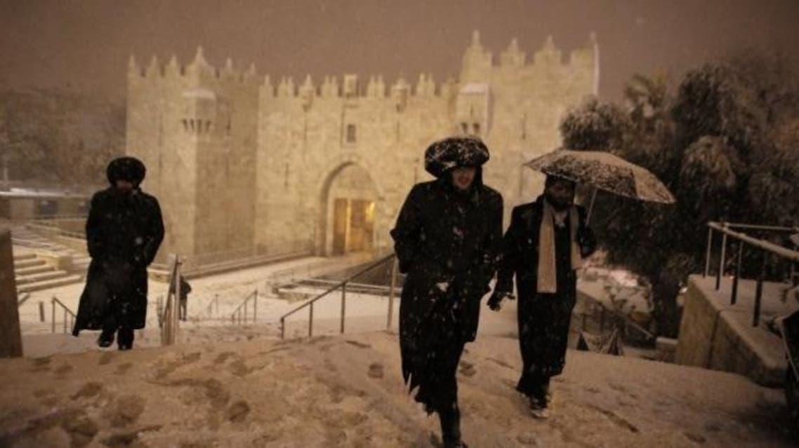 Ultra-Orthodox Jewish men walk near Damascus Gate in Jerusalem's Old City as snow falls on February 19, 2015. (AFP)