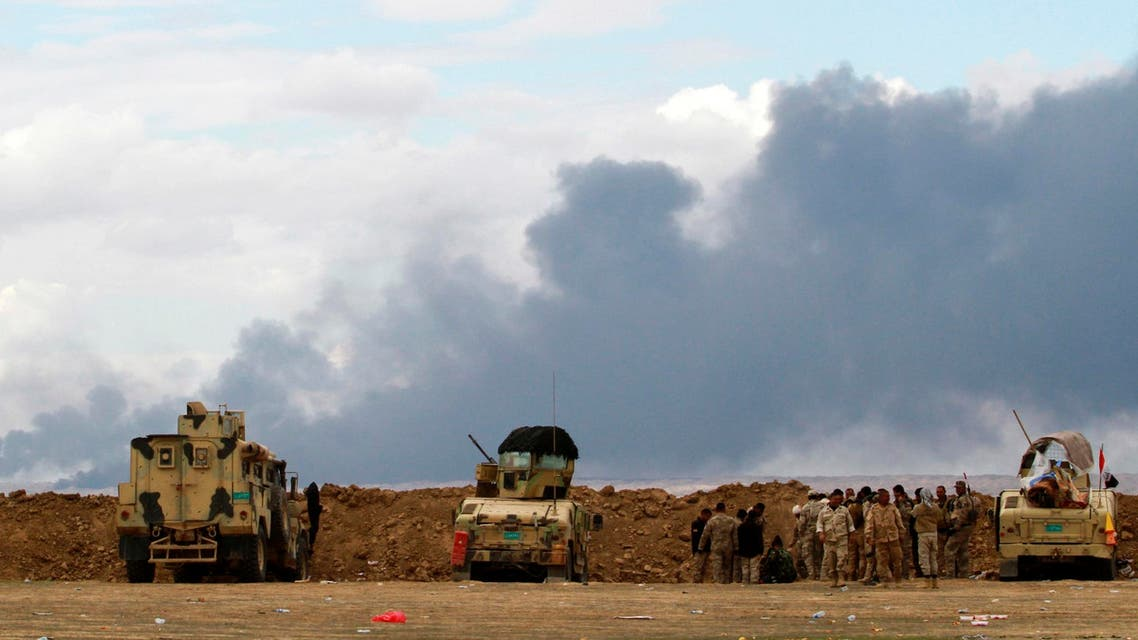 Iraqi soldiers gather near their vehicles as smoke rises from oil wells in the Ajil field east of the city of Tikrit in the Salahuddin province, March 4, 2015.  (Reuters)