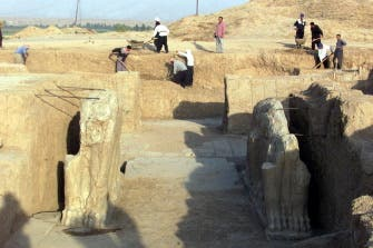 A file picture taken on July 17, 2001 shows Iraqi workers cleaning a statue of winged bull at an archeological site in Nimrud. (AFP)