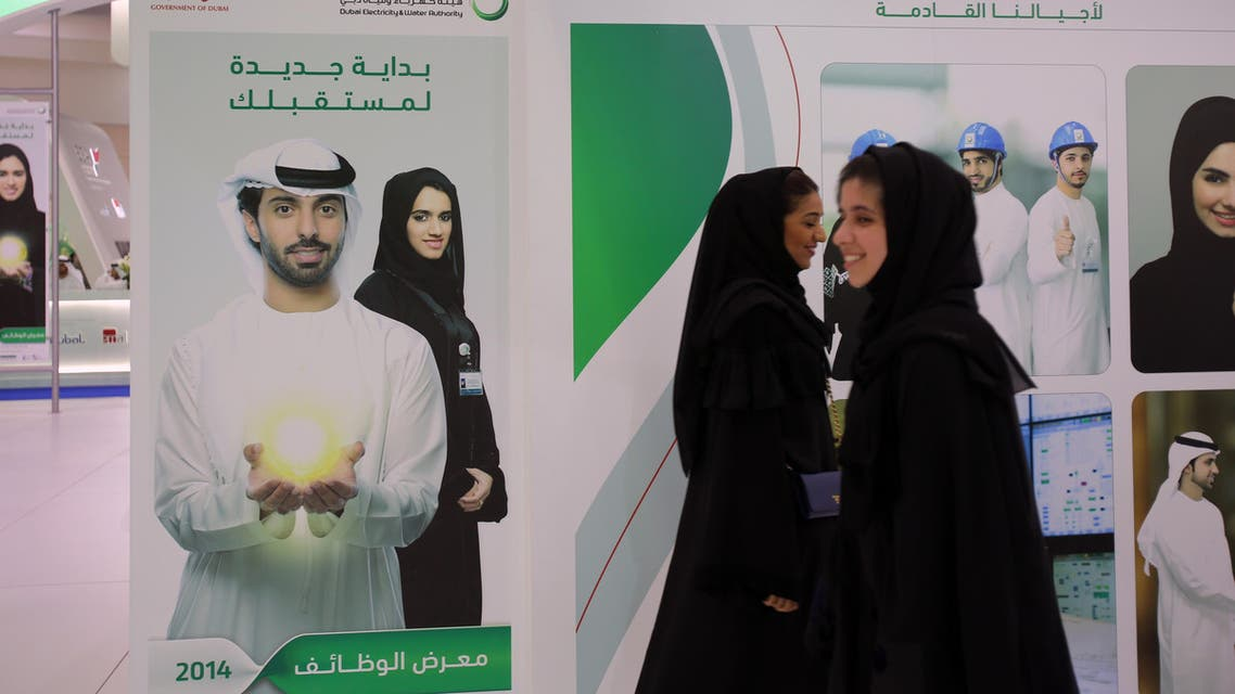In this Tuesday, April 22, 2014 photo, Emirati women pass by posters at a government stand during the Careers UAE opening exhibition exclusively for UAE Nationals in Dubai, United Arab Emirates. (AP)