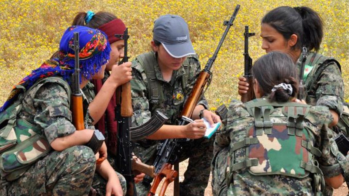 Kurdish female fighters of the Women Protection Unit (YPJ) squat as they discuss military strategies at a training field near Qamishli.(Reuters)