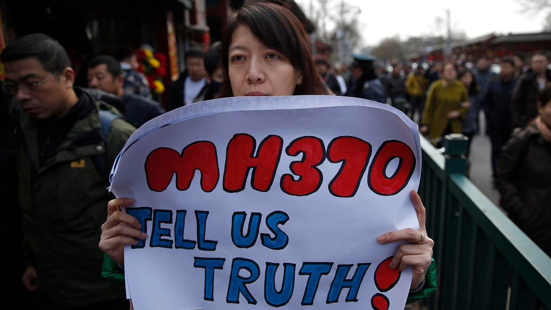 Catherine Gang, whose husband Li Zhi was onboard the missing Malaysia Airlines flight MH370, holds a banner as she walks outside Yonghegong Lama Temple  Reuters