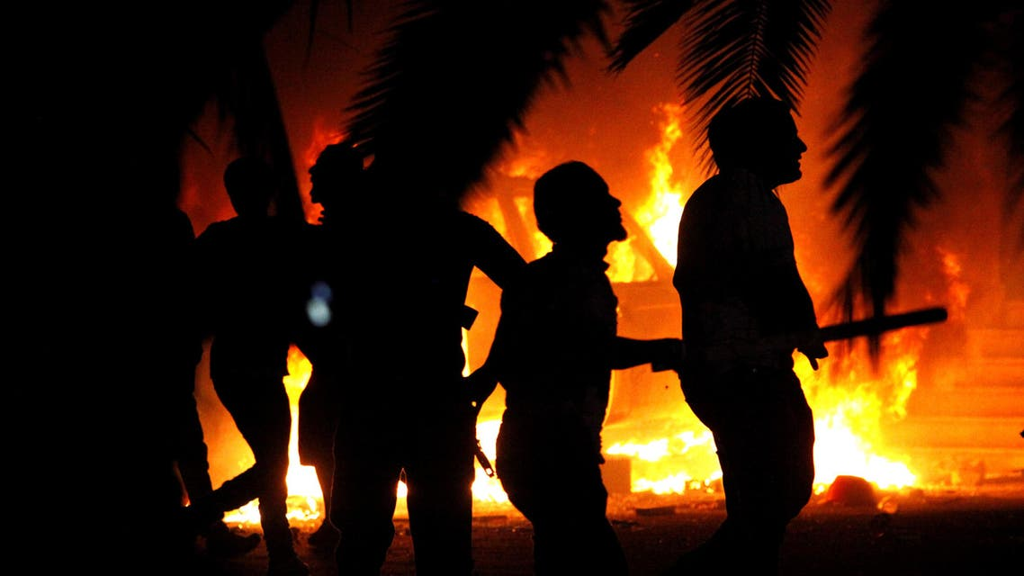 In this file photo, Libyan civilians watch fires at an Ansar al-Shariah Brigades compound. (AP)