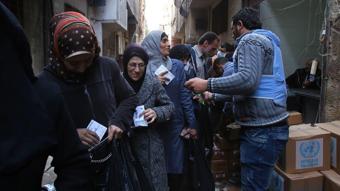 سكان من مخيم اليرموك يتلقون مساعدات الأمم المتحدة