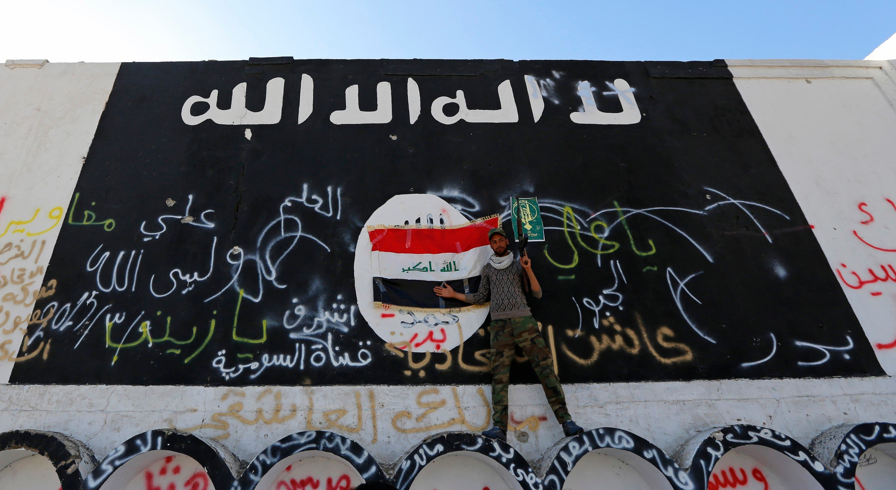 A member of militias known as Hashid Shaabi stands next to a wall painted with the black flag commonly used by Islamic State militants, in the town of al-Alam March 10, 2015. (Reuters)