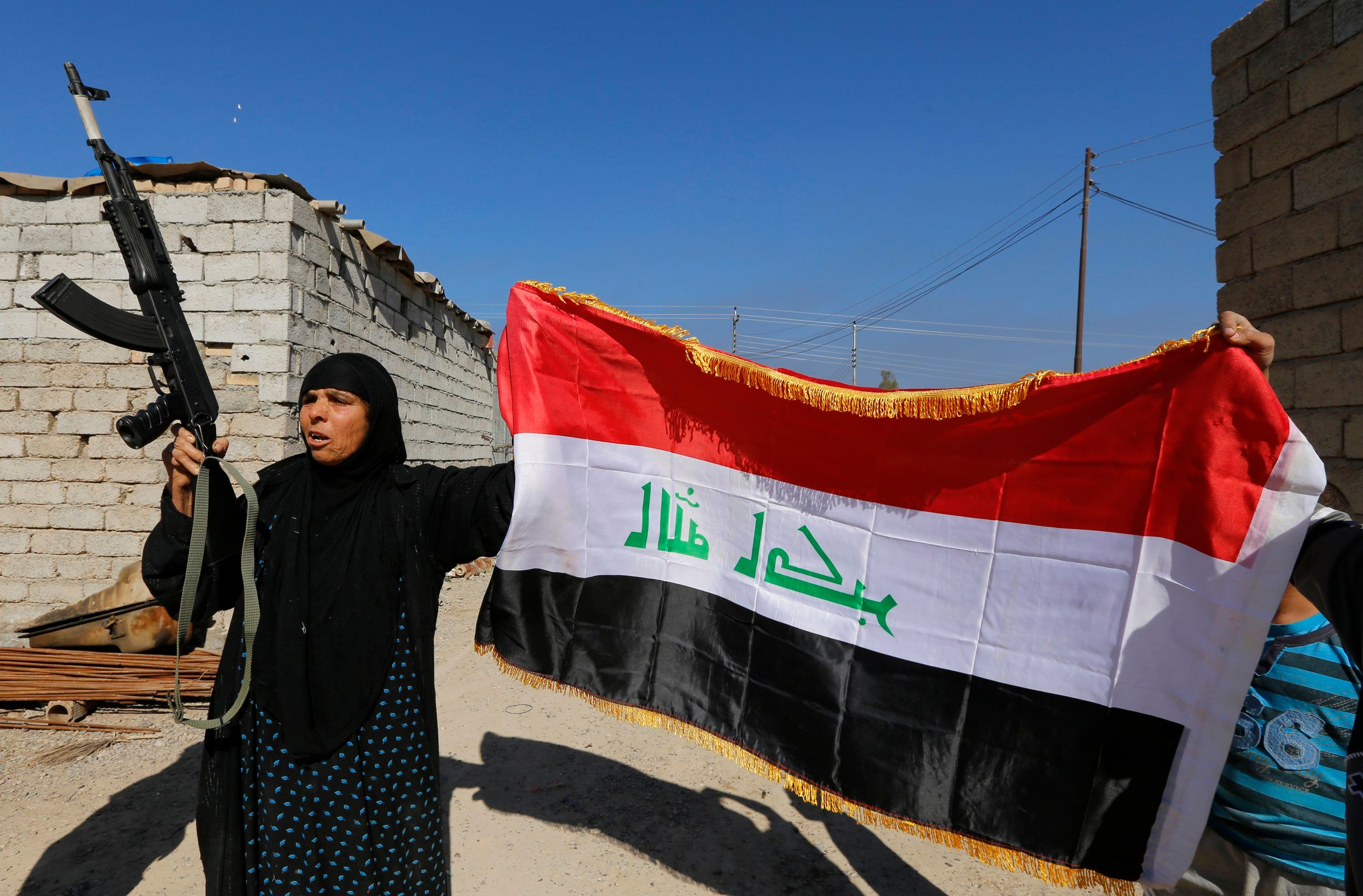 A woman with a weapon and the Iraqi flag welcomes her relative who is part of militias known as Hashid Shaabi, in the town of al-Alam March 10, 2015. (Reuters)