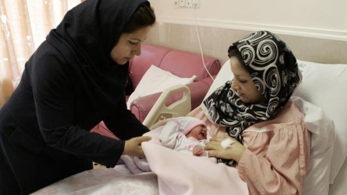 An Iranian nurse gives one-day-old baby girl to her mother at a hospital in Tehran AP